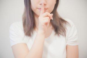秘密のジェスチャーをする女性