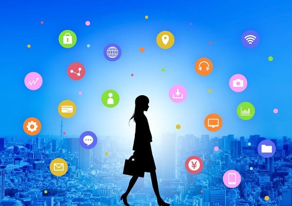 アプリやSNSのアイコンに囲まれ歩くビジネスウーマン