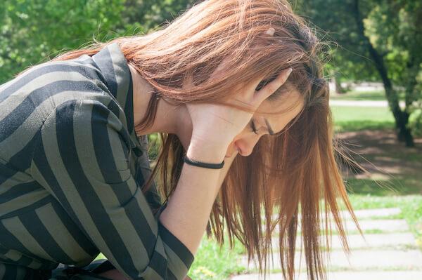 頭を抱えて悲しむ女性